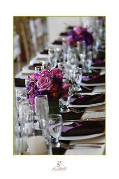 wedding table colors.. white tablecloths, black runner, black napkins, purple centerpiece, purple programs