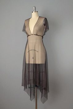 This extremely chic piece from the 1990's is made from chocolate brown net which has a rich silken texture and beautiful liquid movement. Features asymmetrical high-low hem, raw-edged seams both interior and exterior, plunging v-neckline, and beautifully draped caplet style back. A