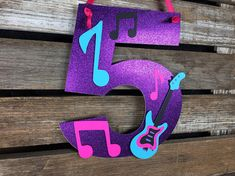 Hang this adorable Rock Star Party Number Sign at your next party! Use it as a door sign or hang it at a gifts table! QUANTITY: 1 - Rockstar Party Number Sign COLORS: Glitter Purple, Turquoise, Hot Pink, Purple and Black. Want different colors? Message me. SIZE: 9 width x 11