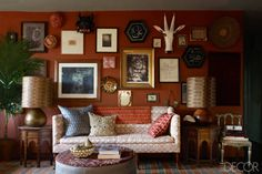russet red wall covered in art + artifacts. the lamps and tables ground the eclectic wall.