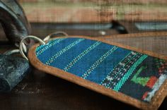 """This one-of-a-kind luggage tag has recycled Huipils (traditional fabric of Guatemala) on one side and a leather pocket on the other, perfect for displaying ID information on a suitcase while standing out at the same time. There is also the word """"Guatemala"""" on the side with the pocket.  Size: Ap..."""