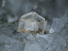 Arisite, Calcioancylite, Aris Quarries, Aris, Windhoek District, Khomas Region, Namibia. Yellow Arisite crystal with small clear Calcioancylites grown in the centre of the crystal surface. Fov 2.0mm. Copyright © Marko Burkhardt