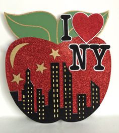 """Here's a big 24"""" glittered apple with a cut out and layered skyline that was used a part of a New York themed centerpiece. Very glittery, big and fun!"""