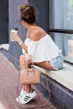 summer outfit, casual outfit, comfy outfit, game day outfit, summer travel outfit, summer vacation outfit, athleisure, sneakers outfit, street style, street chic style - white off the shoulder top, light distressed denim shorts, white sneakers (adidas superstar), nude shoulder bag, aviator sunglasses