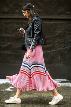 Vibrant midi pleated skirt paired with sneakers and a leather jacket
