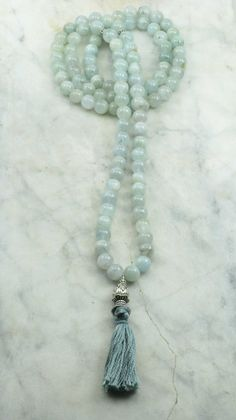 Morning Mist Mala – 108 Aquamarine Mala Beads This peaceful mala is made from 108 blue aquamarine mala beads. This gemstone makes these mala beads excellent for calming, soothing, and peace. These Buddhist prayer beads can be used in meditations that focus on calming. Antiqued silver is used to bring our the detailing of the guru. A lovely artisan crafted lotus pendant from the Himalayas is used as the guru. Gemstone aquamarine has water as its core element, making it an ideal mala for…