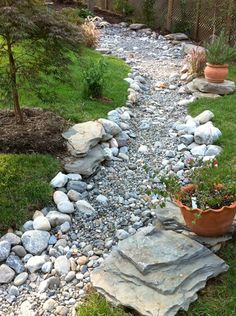 Terra cotta pots on boulders and ornamental trees flanking an organic-looking dry creek bed.