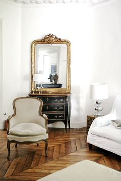 Ornate gold mirrors and louis xv style furniture contrasting with the parquet floor-very glam!