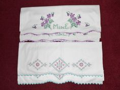 """Two hand embroidered vintage pillowcases. They feature lovely designs. one has green, pink & grey daisy flowers with a geometric design. The other has purple flowers, green leaves and the word """"Mine"""" also in the green leaves. These pillowcases have a crochet ruffled edge. Both sets are the standard size. They are in excellent condition with the exception one purple flowers case has two very small brown spots, about the size of a seed, that may wash out. This bed linen will give your bed a…"""