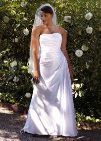 Classic meets chic inthis slim charmeuse gown that is simple yet stunning.  Strapless gown feautres a slimming side-drape that adds dimension and shape.  Beaded applique detail at the waist gives this style and extra touch of glamour.  Soft charmeuse fabricis comfortable and feminine.  Sweep Train. Available in White and Ivory.  Also available in Missy sizes 0-16, Style WG3208,   Fully lined. Back zip. Imported. Dry clean only.  To preserve your wedding dreams, try our Wedding Gown Preserv...