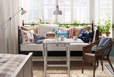 IKEA-sohvasänky makuuhuoneessa. Pöydän edessä pieni pöytä, johon on katettu kahvit.