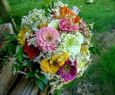 All seven attendants wore bright yellow dresses and carried bouquets of brightly…