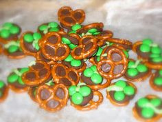 St Patrick's Day Snack  Cover  a cookie sheet with waxed paper and a single layer of pretzels and put a Hershey's kiss on each and every pretzel. Put in the oven at 200 degrees until  melted. Put 3 green M's on each kiss. Put in the fridge until the chocolate is set . Add a line of green frosting to make the stem.