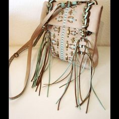 New Isabella Fiore Southwest style crossbody bag Brand new rare Isabella Fiore leather Fringe Benefits Maya.The buffed leather with knotted accents and metallic edge paint make this bag so fun.The tan and turquoise colors compliment each other.Features detachable and adjustable crossbody strap knotted tan and  turquoise trim, metal detailing at the front, back slash pocket lots of fringe at the front of the bag! Foldover closure interior zip compartment plus open multi-function compartment…