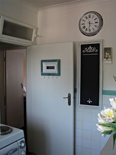 A hand made, framed chalkboard notice board with stencilled design  covers up the distribution board. The picture frame on the kitchen doo...