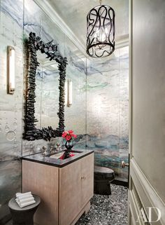 In the powder room of a Manhattan home designed by Michael S. Smith and architect Oscar Shamamian, an Eve Kaplan mirror is set against glass panels by Nancy Lorenz; the hanging lantern is by Paul Marra Design, and the sink fittings are by P. E. Guerin.