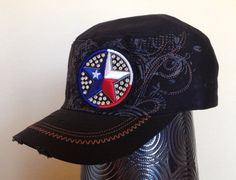 This distressed black cadet cap features a charcoal grey screen printed pattern across the front of the hat, along with brown embroidery that follows the pattern. There is a Texas star embroidered with red, white and blue thread and embellished with silver rhinestones on the front left of the hat and there are pieces distressed/torn over the hat and bill for a fun 'worn' look.  - Three-panel construction. - Embroidered design. - Screen printed design. - Silver rhinestones.