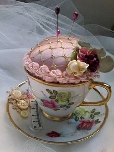 I have repurposed this lovely vintage tea cup and saucer into a unique shabby chic pin/Hat pin cushion. Featuring french vintage trim, buttons and satin flowers this piece would look lovely on a dresser or displayed in a sewing room or china cabinet. Makes a sweet gift for those that love to sew.