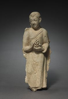 ca. 300. Buddhist Layman Bearing Offerings. high relief stucco placque with bracket. Gandhara.