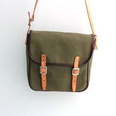 Vintage small canvas bag with leather straps from Poland 80s. This bag canvas has beautiful green color. Long shoulder strap which is long enough to be worn across the body. Two inside compartment. Invisible traces of use. It is very cute and good vintage condition. Dimensions bag: Height 25 cm / 10 width 23 cm / 9 max. length of the strap 72 cm / 28  ------------------------------------------------------------------------- Please feel free to convo me with any questions ------...