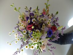 Top view of the Bride's bouquet.  Colourful country style flowers including feverfew, cornflowers, fragrant pinks, delphinium and limonium.