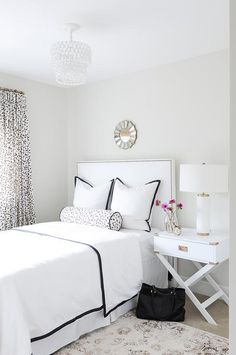 Chic black and white bedroom boasts a tiered pendant, PB Teen Teardrop Flush Mount, illuminating a small gold sunburst mirror lining a soft gray wall placed over a white nailhead headboard on twin bed dressed in black and white border bedding as well as a black and white bolster pillow, which matches the curtains, placed next to a white campaign table and a West Elm Pillar Table Lamp.