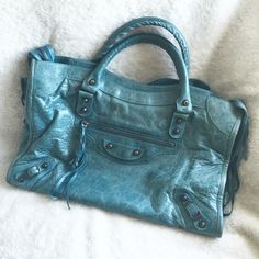 BALENCIAGA Aquamarine Motorcycle City Handbag 2007 Balenciaga Aquamarine Chevre Motorcycle City Bag made of distressed goatskin with stud details  • Pre-loved in excellent condition. Shows slight wear around corners & trim • All edge pictured, one side has tiny wear • Detachable shoulder strap • Mirror not included • Includes all cards & dust bag • Still smells of Goat Leather  • Tassels on zipper are torn/shorter • Tassels on pocket are tied • Handles have some thread sticking out • Slight…