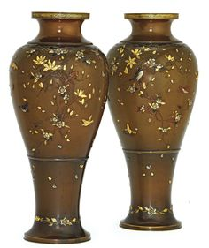 A Pair of Bronze Vases  Signed Shibuya zo, Meiji Period (late 19th century)  Carved in low relief and inlaid in gold, silver, shibuichi and shakudo with birds hovering among cherry blossom and magnolia, many of the blossoms falling towards the base of the vases around which is entwined flower spray and foliage
