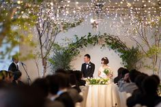 A simple arch of greenery and hundreds of white fairy lights give this wedding reception an airy and fresh feeling - perfect decor for an indoor garden wedding.