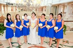 Pop of these bridesmaids' blue dresses against the bride's white gown