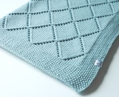 Very soft and lovely hand knitted baby blanket in green turquoise color. Your baby will be warmly covered as this blanket is knitted from 100