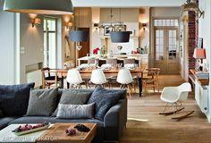 Salon z kuchnią urządzono ciepło, domowo i elegancko. Aranżacja jest spójna, bo ma doskonałą bazę, którą tworzą białe ściany i dębowa podłoga. Oglądając ten salon z kuchnią zwróciliśmy uwagę na oświetlenie - lamp jest dużo i znakomicie budują nastrój wnętrza. Do tego dobrze dobrane meble, gzymsiki, ceglana ściana i mamy salon z kuchnią eklektyczny, ale nie przerysowany.