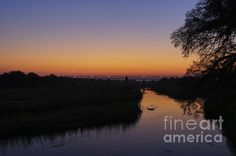 Beautiful sunrise over the Sabie River and a silhouetted bridge in Krugar National Park, South Africa.