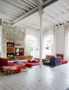 Colourful rustic contemporary loft space with fabulous art floor cushions from Roche Bobois