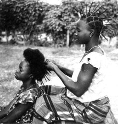 West African Woman, threading hair (with tread) into sections. This is where it all started for us.