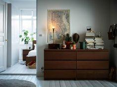 Duas cómodas castanhas com muito espaço para roupa e têxteis de cama. E com espaço em cima para plantas e livros.