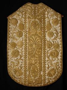 Gold embroidered or pomegranate casula, German, 18th century. The front and back are divided into three sections by strips of embroidered baroque shells resembling braided trim. The outer edges are laced with similarly patterned embroidery stitched on with cord spun from metallic strands. The varying degrees of shininess of the embroidery is produced by using metallic strands or cantille more tightly or loosely spun or cross-sectioned.