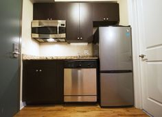 This studio kitchen has stainless steel appliances, including a built-in microwave that doubles as a convection oven and a full dishwasher. #bjbproperties #chicagoapartments #roscoevillageapartments