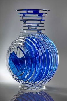 "Vertical Vase #10 17.5""x10""x12"" 2015 A laminated construction of 1/4"" cut and polished glass circles and 1/2"" polished bars. The bars are laminated in a helical pattern between the circles using a blue pigmented, ultraviolet adhesive."
