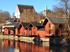 Traditional wooden houses and Medieval church in Porvoo, Finland. The red-coloured wooden storage buildings on the riverside are a proposed UNESCO world heritage site.