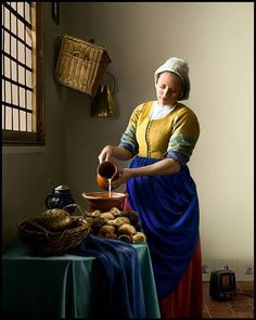 """Costumer/model Angela Mombers and artist/ photographer Carlo Oggioni made a reproduction of """"The Milkmaid"""" by Johannes Vermeer, 1658, Rijksmuseum Amsterdam.  Model, costume: Angela Mombers Photographer: All rights reserved to Carlo Oggioni (www.carlo-oggioni.com) Location: Castle Loevestein  The little electric heater that replaces the foot stove, is a little joke from the photographer. It is his trademark to add a modern element in the photo."""