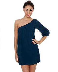 """The First Impressions One Shoulder Navy Blue Dress is perfect for sipping pina coladas on the beach or tasting appetizers at the new art gallery opening! This one-shouldered beauty has pleated detail at the neckline and shoulder, and a three-quarter length sleeve. Dress is lined. Model is wearing a size small. Size small measures 31"""" from shoulder to hem. 17.5"""" sleeve (from neckline). 32"""" bust. 36"""" waist. 100% Rayon. Hand Wash Cold. Made with Love in the U.S.A."""