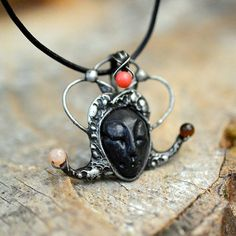 Černý+humor+Malá+černá+keramická+hlavička+a+šaškovská+čepice,+tak+si+představuji+černý+humor+ztvárněný+ve+šperku.+Čepička+je+zdobena+drobnými+korálky+a+to+karneolem,+korálem+a+tygřím+okem.+Velikost+celého+šperku+je+3,5+cm+x+4+cm.+Zavěšen+je+na+koženém+černém+řemínku+o+délce+45+cm.+ZPŮSOB+ZPRACOVÁNÍ:Šperk+jeručně+pocínován+bezolovnatou+cínovou...