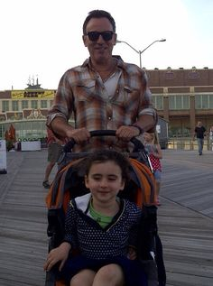 Bruce Springsteen poses with a fan's young daughter on the boardwalk in Asbury Park.