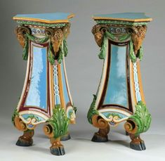 """Pair of Continental majolica ram's head pedestals in the Neoclassical taste, circa 1880, having triangular tops in turquoise with mustard rims surmounting conforming standards each having three ram's heads conjoined by green foliate swags, above turquoise, mustard, and burgundy molded panels, leading to scrolling acanthus knees, and each rising on figural hoof feet, 38.5""""h x 23""""dia."""