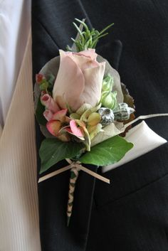The Groom's Boutonniere of fresh Rosemary, an Amnesia Rose, Ranuncula Buds, Rolled Rose Petals, Hydrangea Florets and Eucalyptus Boules enveloped in a Skeleton Leaf and framed by Ivy & Galax Leaves and finished with Champagne Ribbon