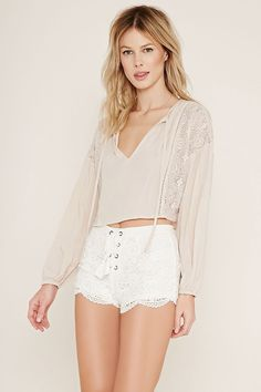 A pair of knit floral crochet shorts with a concealed back zipper, scalloped hem, and a lace-up front with grommets.