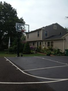 A two story home sits in the background of a nice blacktop backyard court with white striping and Pro Dunk Gold basketball system. Basketball Systems, Basketball Goals, Backyard Basketball, Two Story Homes, New Homes, Outdoors, Exterior, Nice, Gold