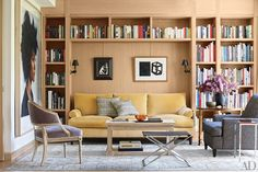 Neal Beckstedt Studio designed the interiors, furnishing the library with a Roman Thomas sofa, a Christian Liaigre club chair, and a vintage André Arbus cocktail table and Poul Kjærholm stool; the large artwork is by Chuck Close, and the black-framed piece above the sofa is by Kara Walker.