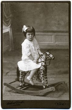 Vintage photo of a little girl on her rocking horse. 1910.